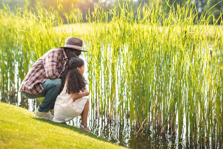 african american granddaughter and her grandfather sitting near lake in park Banque d'images - 102894107