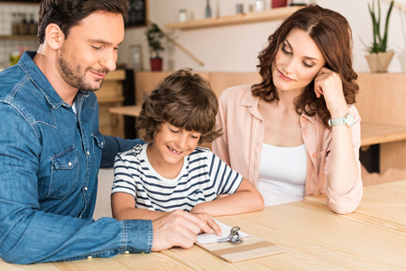 beautiful young family in cafe looking at paycheck Stock Photo