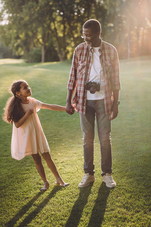 african american man with camera holding hands with his granddaughter and standing on green lawn in sunlight