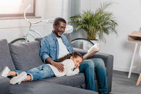 African american man reading book for his adorable daughter sleeping on his knee Archivio Fotografico - 102355715