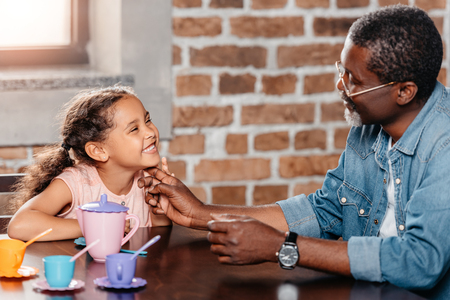 African american girl having tea party with father at home Foto de archivo - 102894114