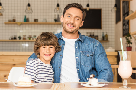 cute smiling son and father sitting in cafe