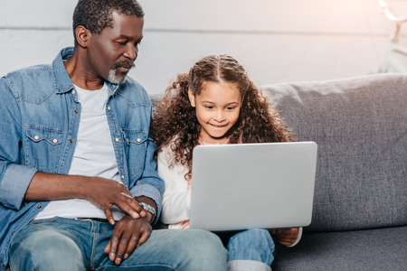 adorable african american girl using laptop together with father at home Stock Photo