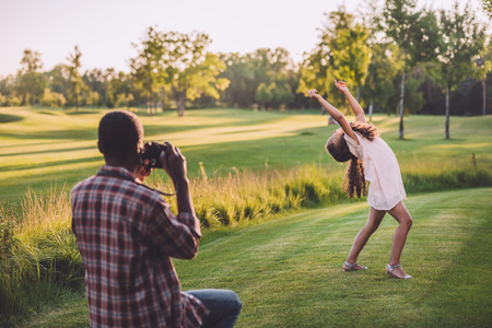 african american man taking photo of his granddaughter playing on green lawn