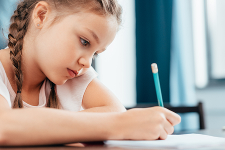 focused serious little girl writing homework Standard-Bild