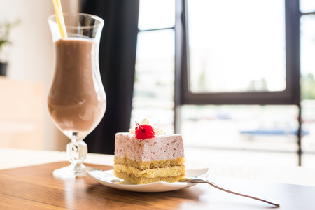 tasty piece of cake and glass of milkshake in cafe Imagens