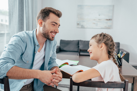 young father doing homework with little daughter