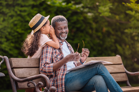 little adorable african american grandchild whispering to her smiling grandfather while sitting on bench in park Stockfoto