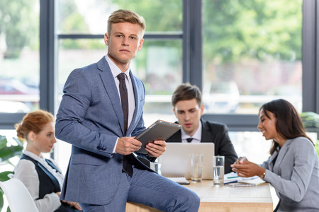 Confident businessman in front of his colleagues in modern office
