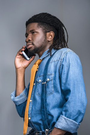 stylish serious african american man talking by smartphone isolated on gray
