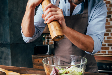 cropped shot of man adding pepper with mill into salad