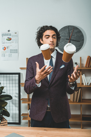portrait of focused businessman juggling with disposable coffee cups in office