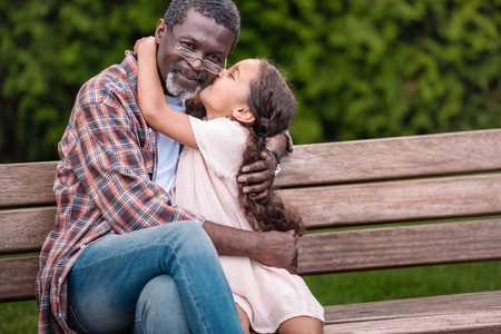 adorable african american girl hugging and kissing her grandfather while sitting on bench in park