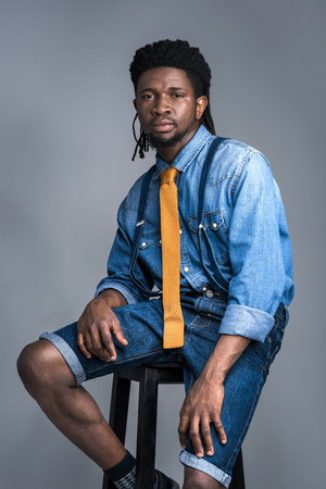 handsome african american man sitting on chair isolated on gray 写真素材