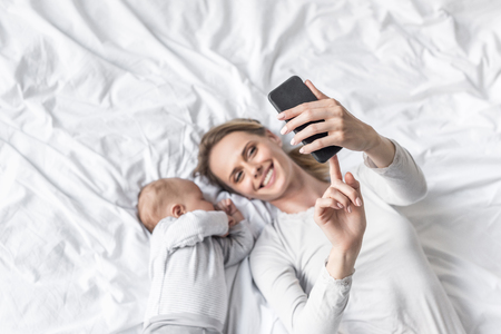 happy mother taking selfie with little sleeping baby
