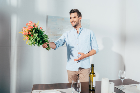 handsome young man stretching out beautiful bouquet