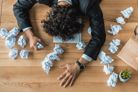 overhead view of tired businessman lying on table with crumpled papers