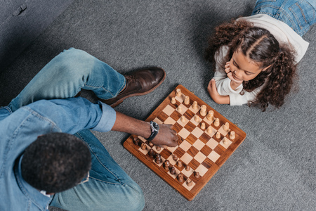 Cute african american girl playing chess with father on floor at home Stok Fotoğraf