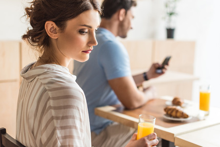 addicted man using his smartphone and unhappy woman sitting on foregroung