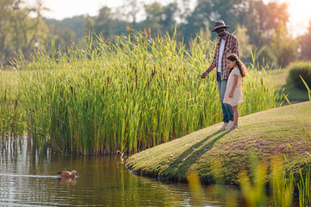 african american granddaughter and her grandfather feeding duck on lake in park Banque d'images - 102359281