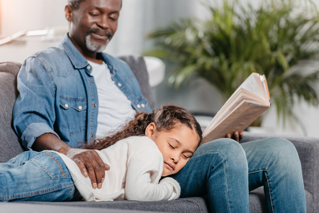 African american man reading book for his adorable daughter sleeping on his knee