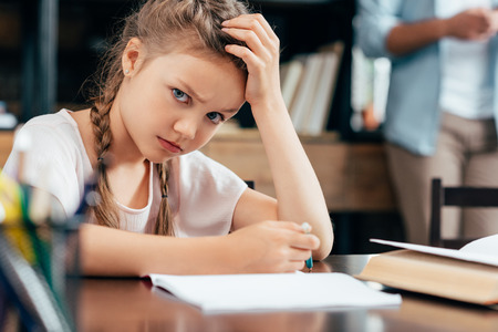 angry little girl writing homework and looking at camera Stock fotó