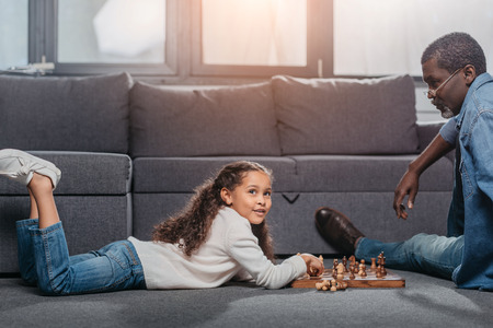 Cute african american girl playing chess with father on floor at home 版權商用圖片