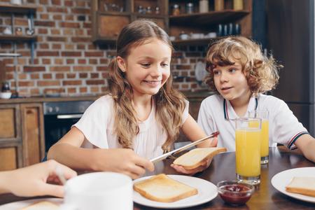 happy little kids having breakfast before school