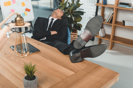 tired businessman with legs on table sleeping at workplace with digital tablet in office
