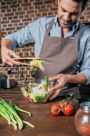 hübscher junger Mann, der Salat mischt Standard-Bild