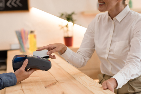 partial view of smiling woman making payment with credit card in cafe 写真素材