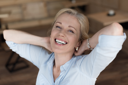 portrait of cheerful mature woman with hands behind head smiling at camera Фото со стока