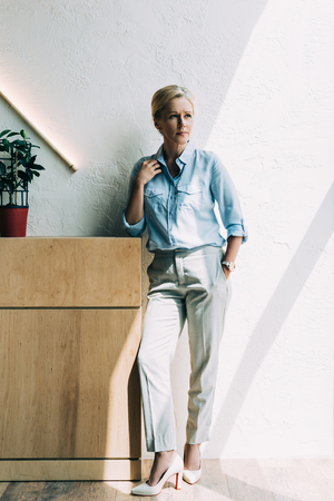 stylish mature woman looking away while standing near wooden commode