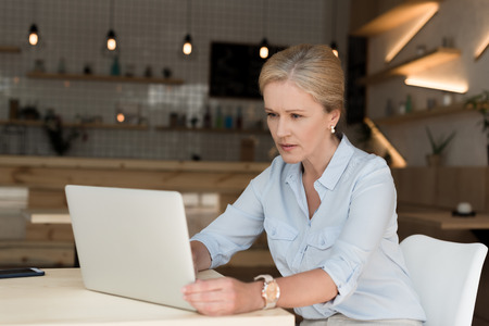 serious mature businesswoman using laptop in cafe