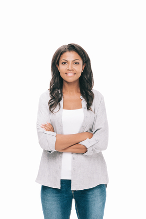 portrait of beautiful young african american woman with crossed arms smiling at camera isolated on white