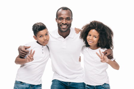 happy african american father with kids embracing and smiling at camera isolated on white