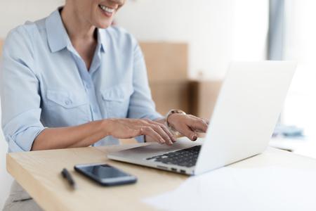 cropped shot of smiling mature businesswoman using laptop