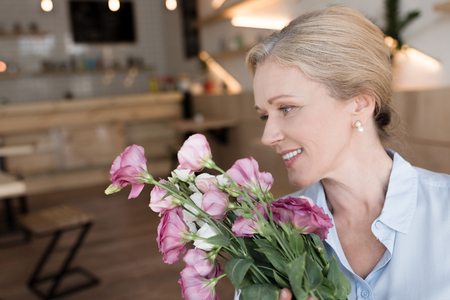 happy mature woman holding bouquet of beautiful flowers indoors