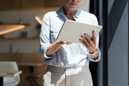 cropped shot of serious mature woman using digital tablet indoors