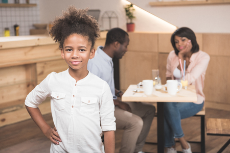 adorable afro girl in cafe with her parents blurred on background