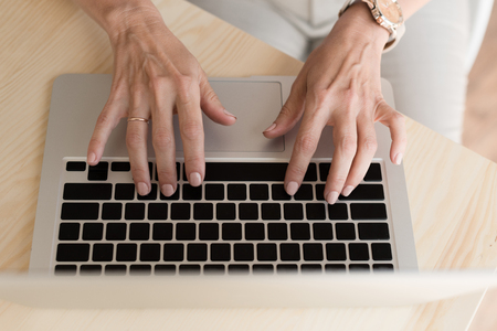 cropped shot of mature woman typing on laptop