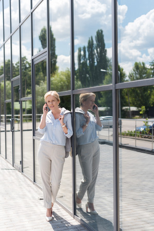 beautiful mature woman talking by phone while standing outside modern building