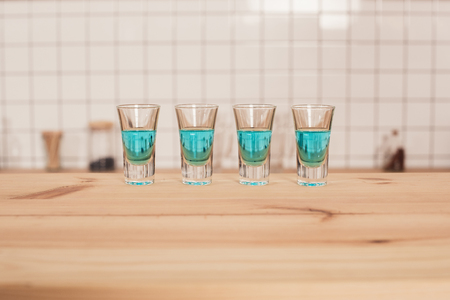 blue cocktails in shot glasses standing on bar counter