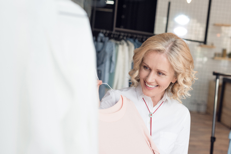 smiling mature woman choosing clothes in clothing store Stockfoto