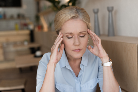 stressed mature woman with closed eyes having headache while sitting indoors Foto de archivo