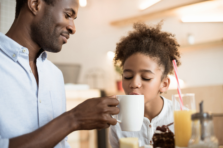 african-american father and cute daughter in cafe
