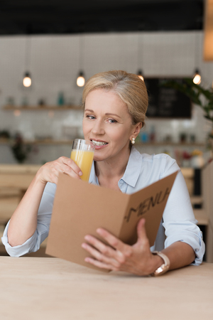 attractive mature woman reading menu and drinking orange juice in cafe 版權商用圖片