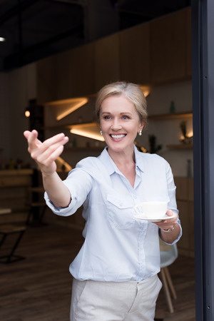 cheerful mature woman drinking coffee and gesturing with hand and inviting in cafe