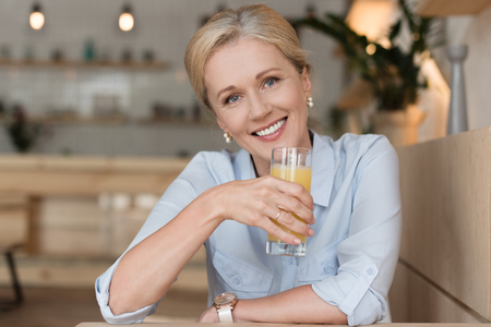 beautiful mature woman drinking orange juice and smiling at camera in cafe