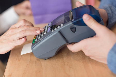cropped shot of woman making payment with credit card in store